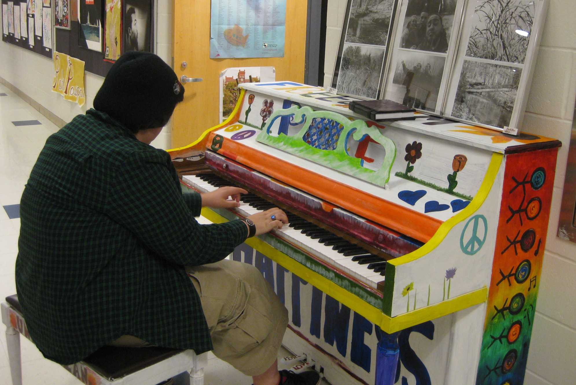 Junior Meagan Martel plays the peace, love, and hope piano at the Art Show. | by Stephanie Petrovick