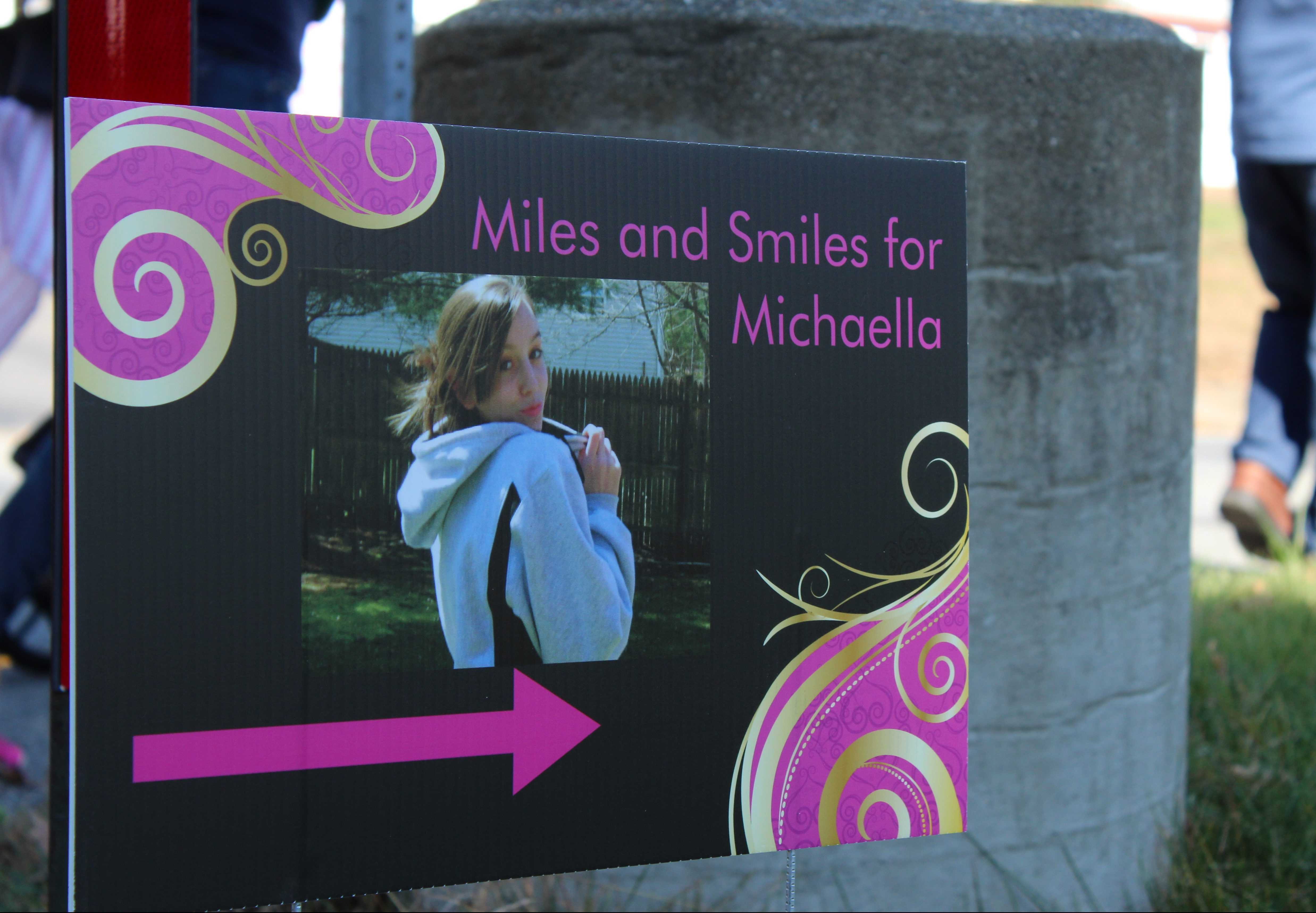 Signs posted along the walk guiding participants through the race depict Michaella throughout her life. | by Siobhan Richards