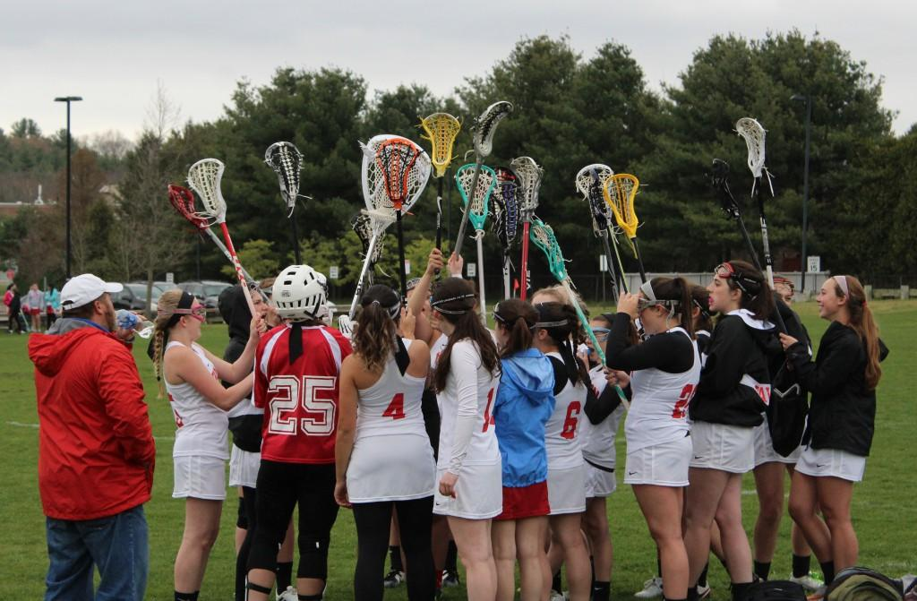 The girls cheer and hold their lacrosse sticks in the air as they enter the second half of the game.