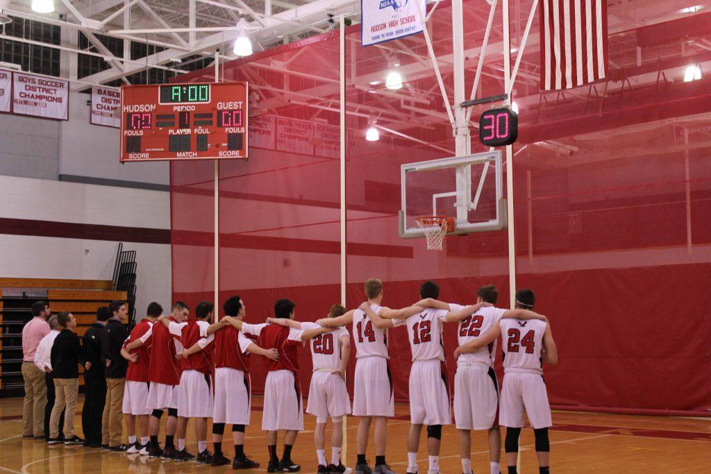 The entire team stands together, looking up at the flag during the National Anthem. | by Serena Richards