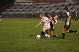 Senior Josie Saliga begins to fall while fighting Oakmont for the ball. | by Ally Jensen