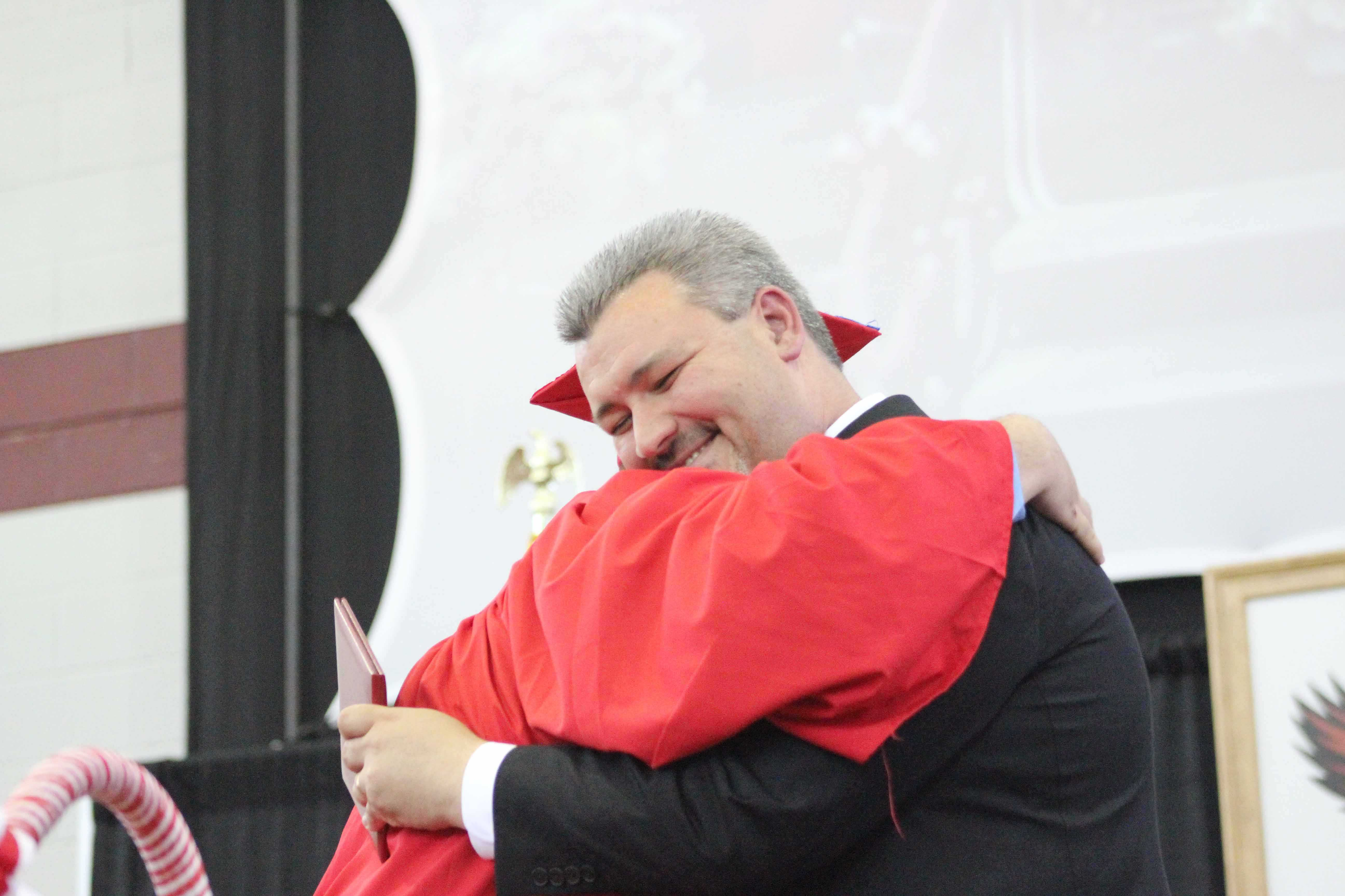 Jordan Bushey gives Principal Reagan a hug instead of a handshake.  |by Ally Jensen