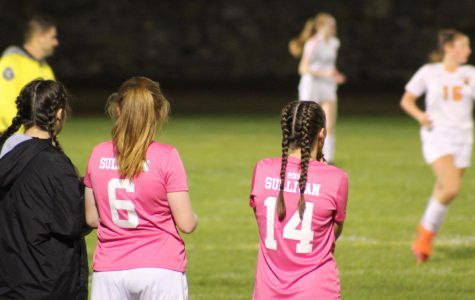 Sophomores Ainsley Majer (6) and Sarah Korowski (14) watch their teammates from the sideline | by Zahara Abdullah