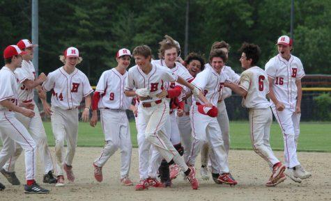 Team celebrates after Jason Jakobsons (15) scores winning run |by Brianna Devlin