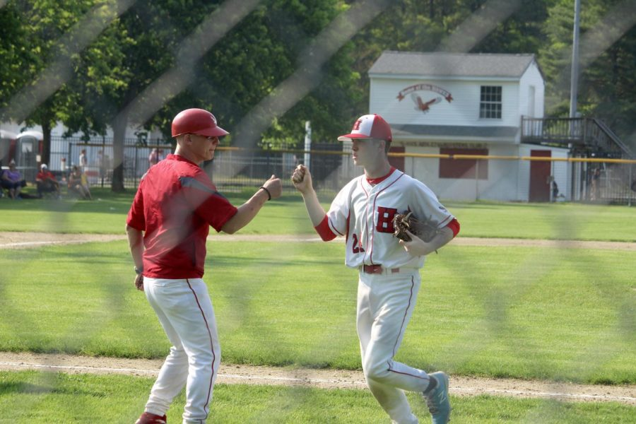 Player gives a fist pump to coach after a great inning  by Brianna Devlin